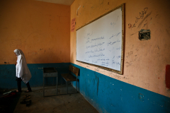 A girl is getting back to her seat after writing on the white board, in a school for girls in Jalalabad