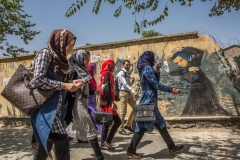 Students, with a majority of girls, on their way to Kabul University. On the wall behind, a painting done by the woman artist Shamsia Hassani