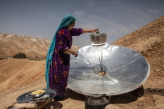 A woman is cooking potatoes using a solar oven . Potato is an important food crop in the region. Often part of a meal, it can help for sustainable  food security