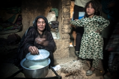 Mother boiling milk to make yoghurt in Bamyan. All the family live in a very tiny mud house with no electricity and no water