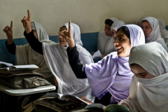 Girls raising their finger to answer to a question asked by the teacher in a school in Jalalabad