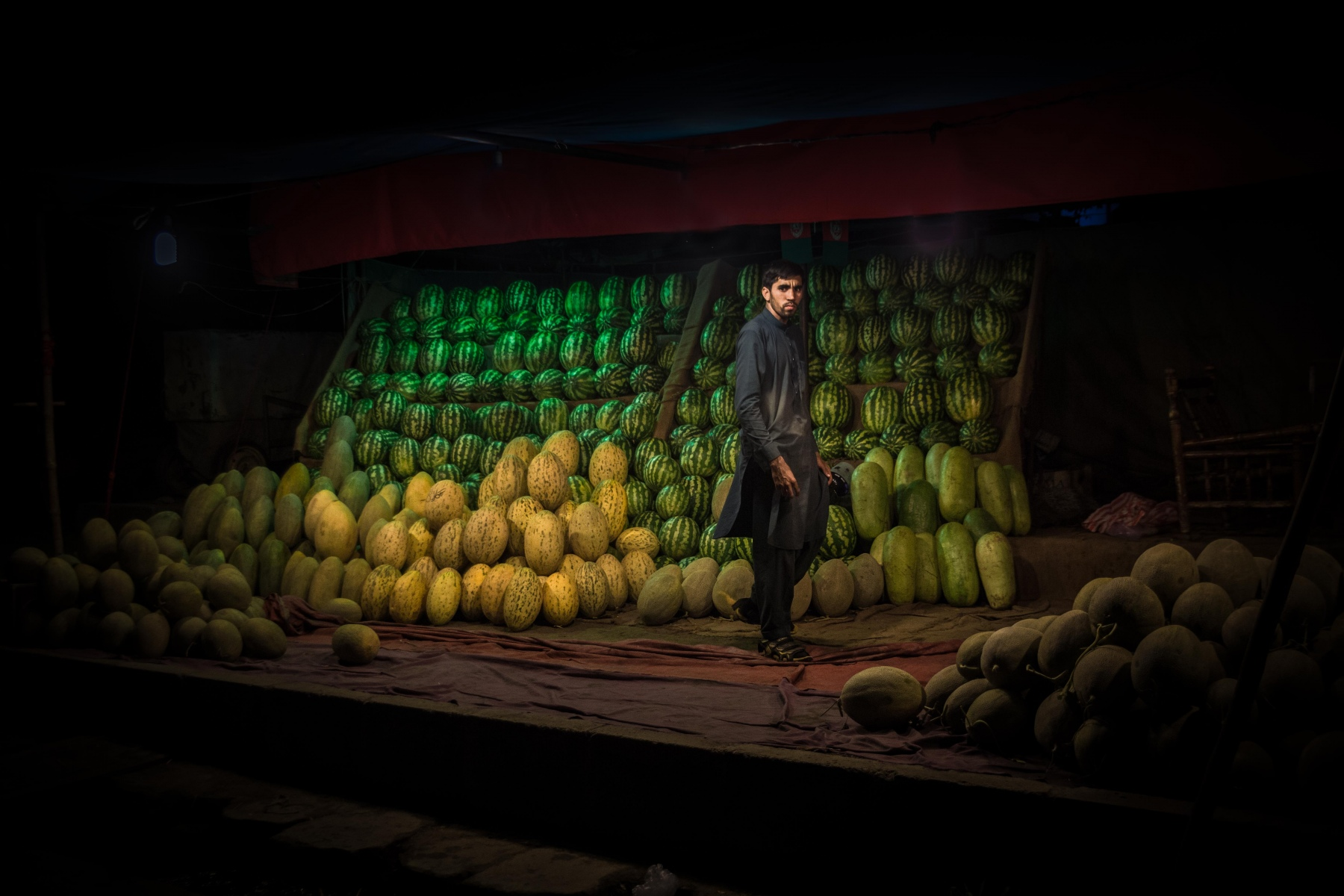 Man selling melons and water melons on a market in Kabul during the night