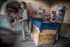 Men making bread in the back side of a bakery in Jalalabad